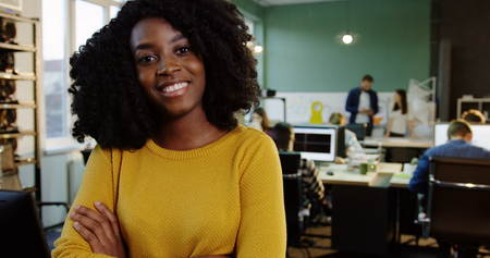 Portrait shot of young attractive curly African American woman smiling into the camera in the modern office. Working people on the blurred background. Close up.