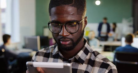 Close up of young handsome African American man in glasses working on the tablet and smiling into the camera in the modern office. Working people on the blurred background. Portrait shot