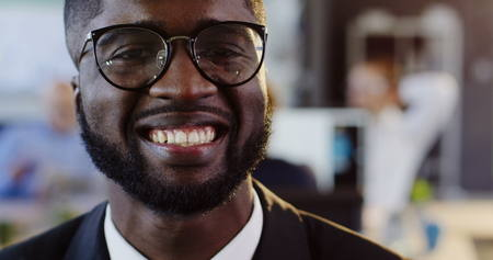 Close up of African American young attractive man in glasses looking on the side and than smiling straight into the camera. The blurred office with workers background. Portrait. Indoor Stock Photo