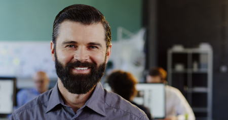 Close up of attractive young man with a beard looking and smiling into the camera. The blurred office with people at computers background. Inside. Portrait Stok Fotoğraf