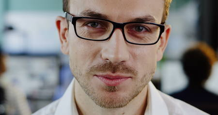 Close up of Caucasian handsome man in glasses looking and smiling sincerely straight into the camera. The blurred office room background. Portrait shot