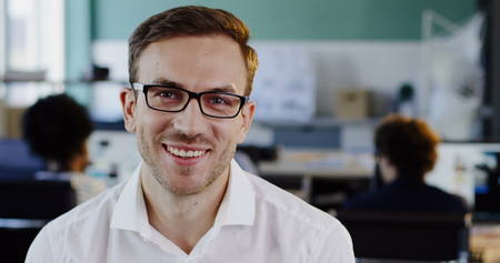 Close up of Caucasian handsome man in white shirt in glasses looking straight in the camera and smiling cheerfully. The blurred office background. Portrait. Indoors Stok Fotoğraf