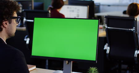 Office worker taping on the PC computer with green screen in the office space. Back view. Chroma key. Indoor
