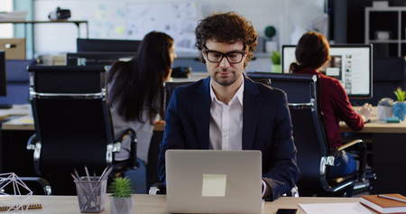 Handsome man in glasses working on the laptop in the big modern office space with others office workers on background. Inside