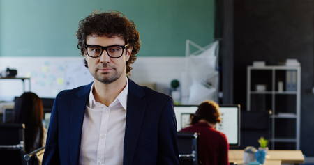 Portrait shot of attractive caucasian young man looking into the camera and taking off his glasses. The blurred office with workers at computers behind. Indoors