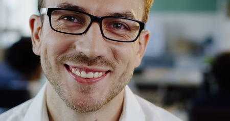 Close up of Caucasian attractive young man in glasses looking and starting to smile sincerely into the camera. The blurred office space background. Portrait shot. Indoor Stock Photo