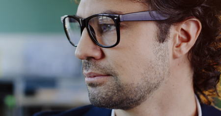 Close up of attractive caucasian man in glasses looking on the side, than smiling into the camera. The blurred office space behind. Indoor. Portrait shot