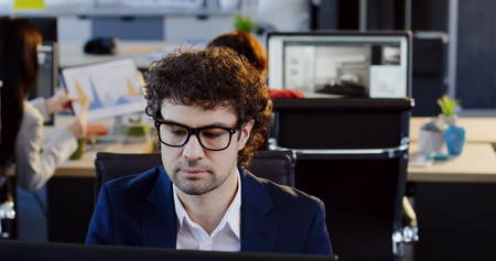 Portrait of serious attractive man office worker in glasses working on the computer and talking on the mobile phone in the modern office. The blurred space with workers at computers on the background. Indoor
