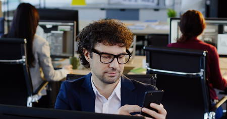 Portrait shot of curly attractive man in glasses scrolling on the mobile phone while sitting on his workplace in the office. The background of working office employees. Indoors