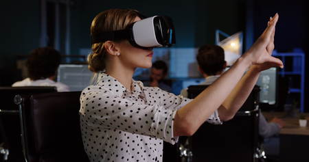Young female office worker having a VR headset at her workplace in the evening. VR glasses.