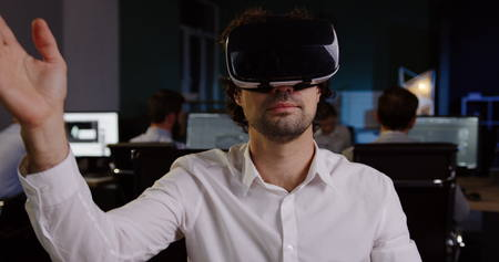 Young curly male office worker having a VR headset at his workplace in the evening. Stok Fotoğraf
