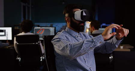 Male office worker with a beard having a VR headset at his workplace in the evening.