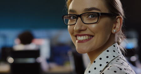 Close up of beautiful woman in glasses looking at office space behind her, than turning the head to the camera and smiling sincerely.
