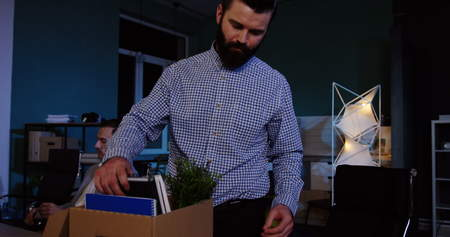Close up of young caucasian man with a beard packing his stuff inside the box in the office at late evening because he lost his job. Stok Fotoğraf