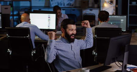 Businessmen and office workers gets excited by job done well on the computer and punches the air in late night.