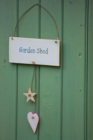 Green painted garden shed door with sign Stock Photo