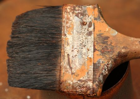 Old and very worn paint brush on a rusty tin