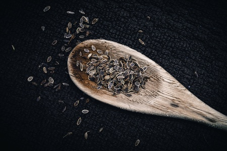 Dill seeds on wooden spoon against black background