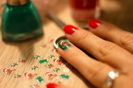 hands of a young woman who paints her nails red and green nail polish and decorate nails decorative sticker with a Christmas theme Stock Photo