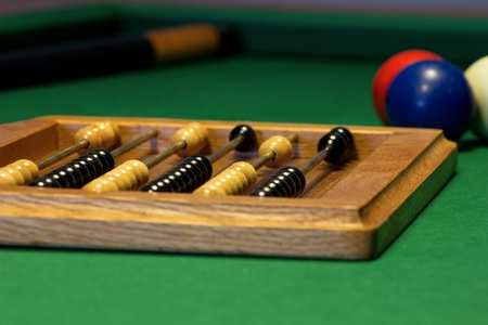 Three billiard balls on a billiard table with a cue stick and chalk and a counter points