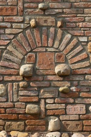 old brick wall: old brick wall with decorative bricks and natural stones between them