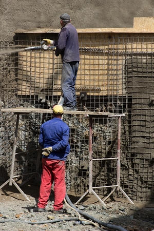 Two men are spraying concrete on a wire construction reinforcing a slope Stock Photo