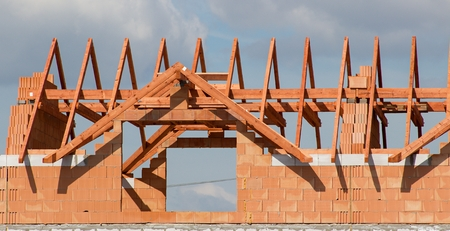 residential construction: Unfinished building of a residential building with a truss on the construction site