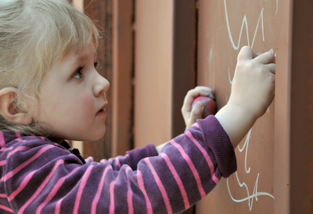 no boundaries: Little girl draws a chalk on the gate. For creativity has no boundaries.