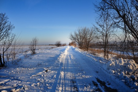winter landscape: snow-covered road stretches into the distance and a cloudless sky Stock fotó