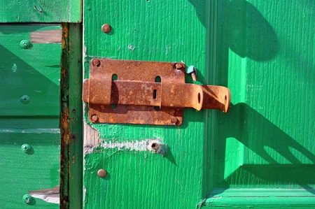 door bolt: green door with a rusty bolt  of the old wooden house Stock Photo