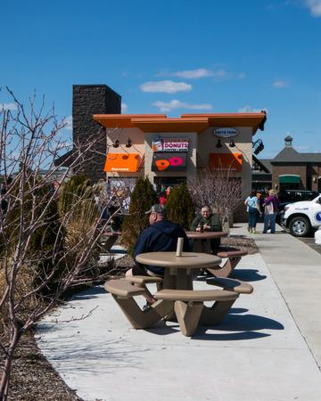 tomando refresco: Las personas que toman refresco fuera de Dunkin Donuts Editorial