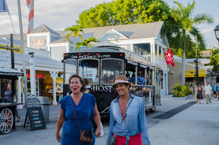 tourists having fun in front of a trolley in key west