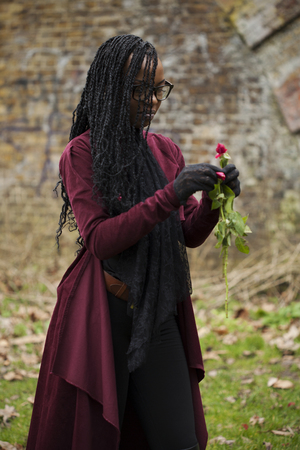 Woman in Glasses Picking Rose Petals in front of Brick Wall Stock Photo