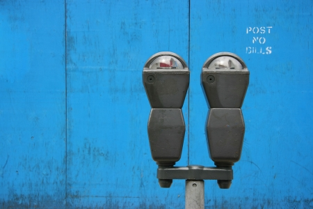 Two parkmeters over blue wooden panels with a stenciled  photo