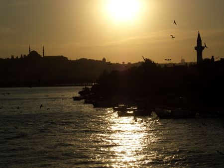 Istanbul skyline seen from Galata bridge over Golden Horn at sunset photo