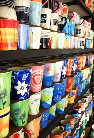 Many coloured tea cups on a shop shelf