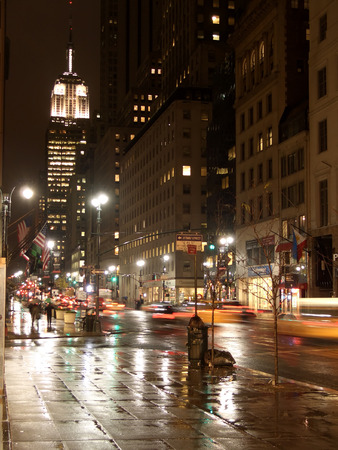 5th avenue and Empire State building by night under the rain, New York