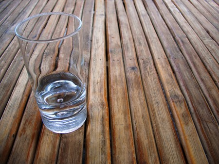 uncluttered: Near empty glass on a wood table top made from listel Stock Photo