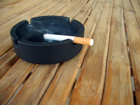 Ashtray with lit cigarette on a wooden table photo