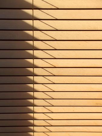 Sun passing through wooden venetian blinds,