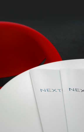 Presentation brochures on a table, red chair, business environment. Focus on brochures cover. photo
