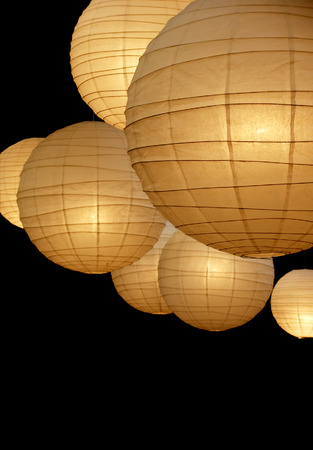 Many warmly colored balloon paper lamps isolated on black background Stock Photo