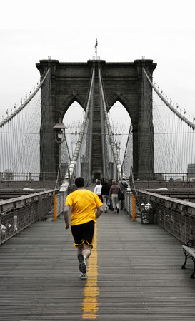 Running on Brooklyn bridge, New York. Yellow and desaturated colors. Stock Photo - 1374104