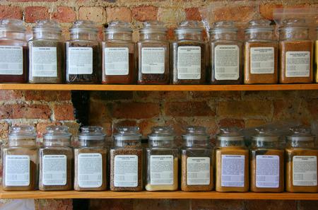 Spice jars on wooden shelf on a brick wall