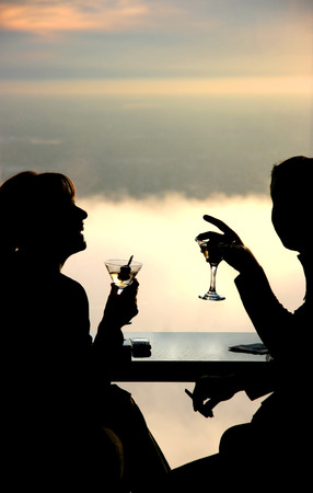 Silhouette of a young couple drinking and having fun. Top floor skyscraper lounge window at sunset 스톡 콘텐츠