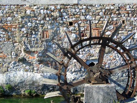 molino de agua: Objetos de rueda de molino de agua oxidado y muro de piedra