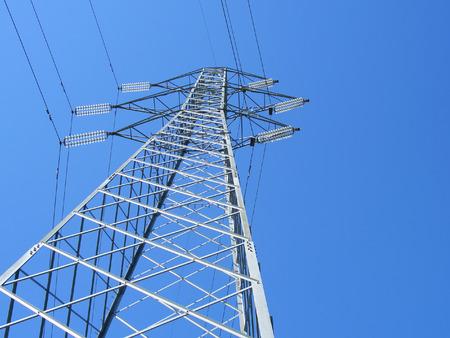 Powerline tower seen from below against blue sky photo