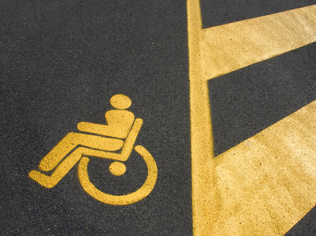 Yellow disabled parking on dark asphalt with marked area Stock Photo