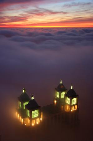 Beleuchtete Wolkenkratzer Anfang peeking aus den Wolken bei Sonnenuntergang wie aus Chicago Hancock Tower  Lizenzfreie Bilder