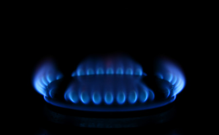 Blue flames from a gas stove glowing in the dark photo
